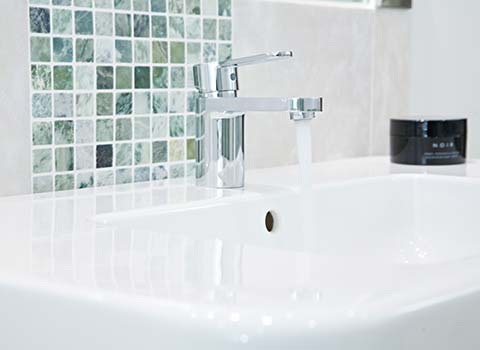 Property Interior - Bathroom basin with water flowing from tap