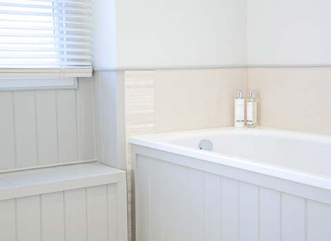Property Interior - bathroom with bath next to a window with blinds